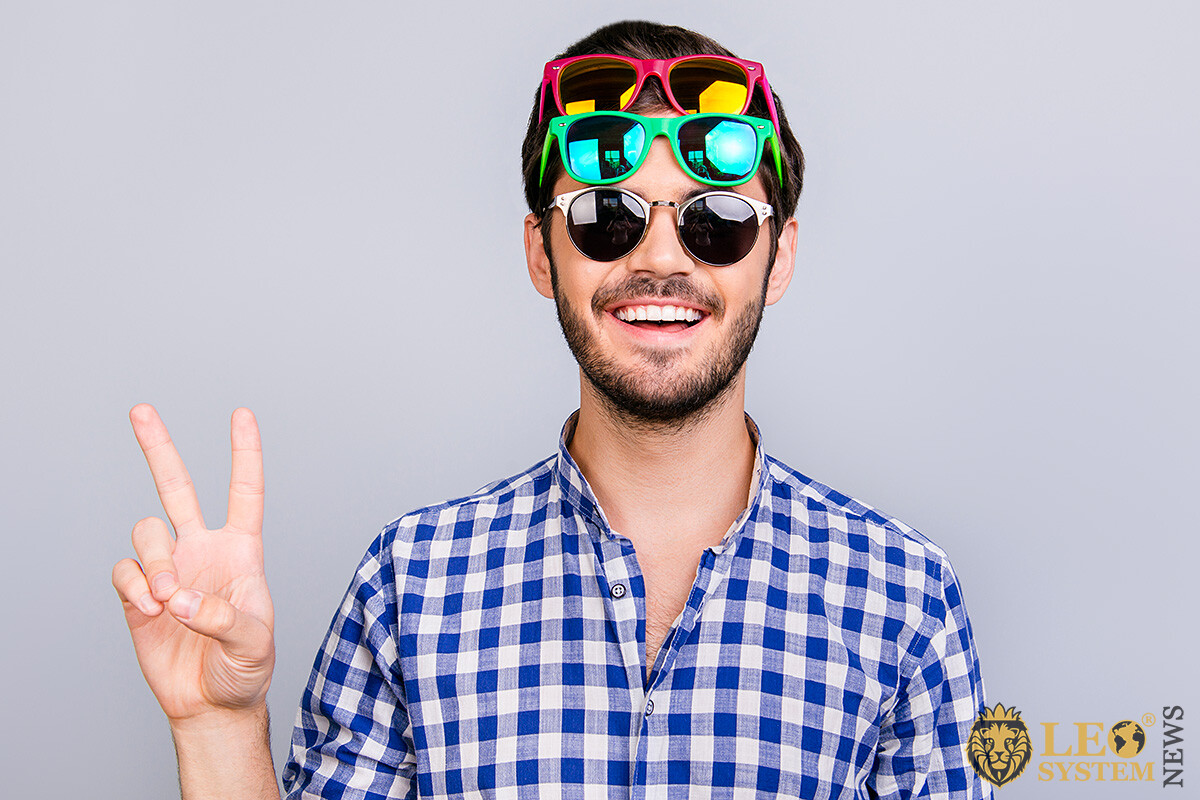 Image of a positive young man with many sunglasses on his head