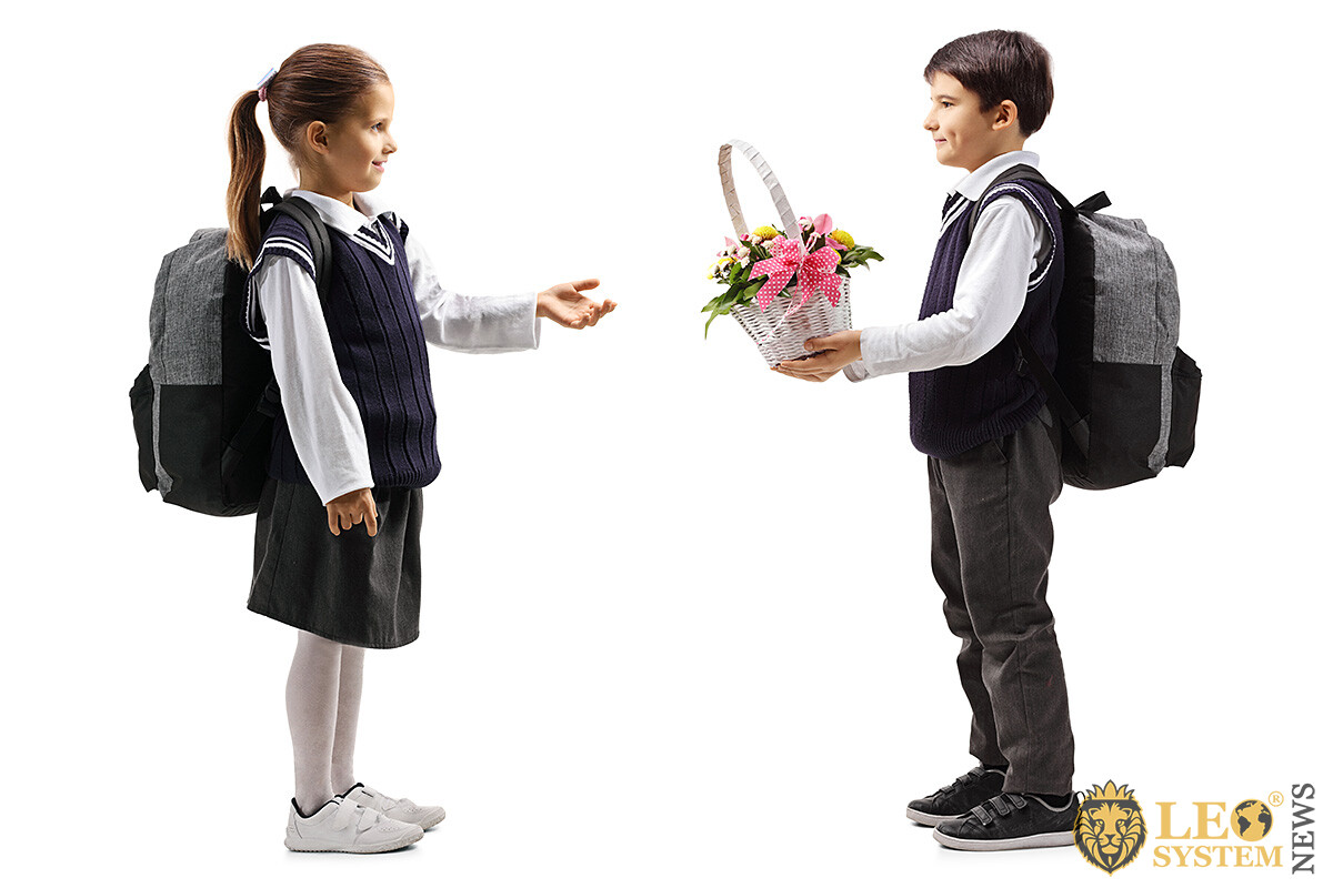 Boy gives a basket of flowers to his school sweetheart