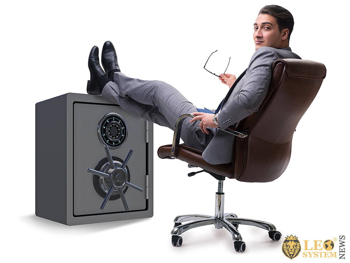 Successful business man sitting near his safe